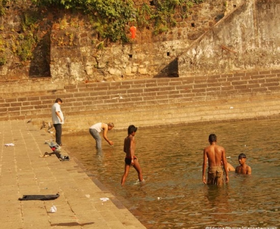 A man immersing ashes while the kids take a bath - banganga tank mumbai