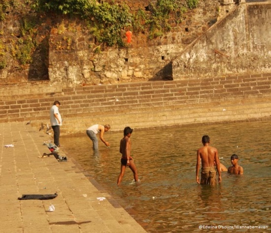 A man immersing ashes while the kids take a bath